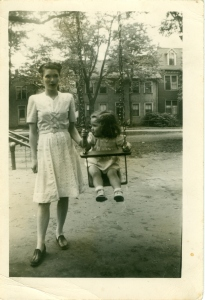 A child and her relative play on the swings in King Square, c. 1950